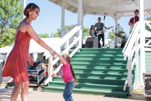 Mother and daughter dancing in front of gazebo